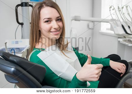 Young Female Patient With Braces On Teeth Sitting In Dental Chair, Smiling And Showing Thumbs Up Aft