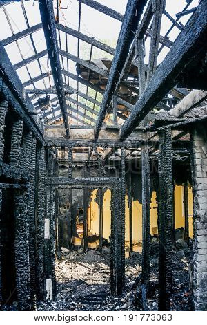 Burnt interiors of house after fire.Charred ceilings and supports. Burned wooden walls, vertical image