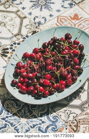 Fresh ripe sweet cherries in blue plate over colorful oriental ceramic tiles background, selective focus. Summer food concept
