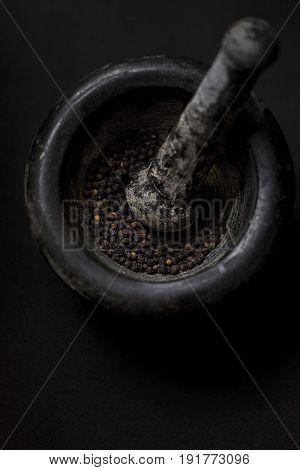 Black peppercorns in black mortar on dark background
