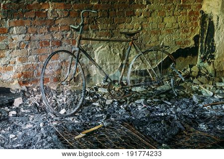 Burnt-out bicycle in old abandoned burnt house