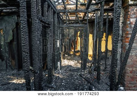 Burned down wooden apartment house, charred walls, burnt roof, black ceilings and supports