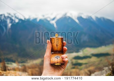 Compass in the hands on background a blue mountain top