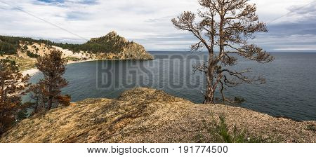 From a high cliff offers a scenic view on a small sandy Bay surrounded by mountains on the shores of lake Baikal.