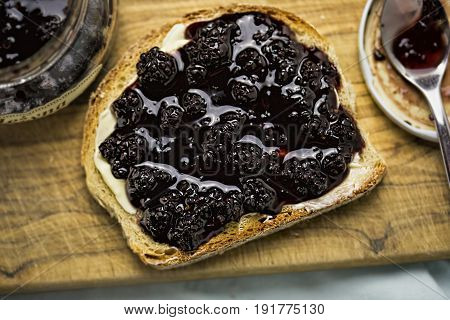 Bread with butter and blackberry confiture on wooden board
