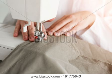 Anonymous woman sewing with machine in atelier.