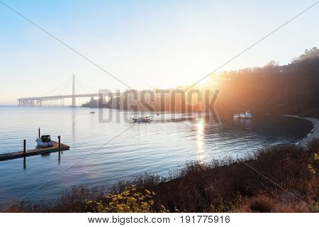 landscape of small yacht pier near Golden Gate Bridge at sunrise