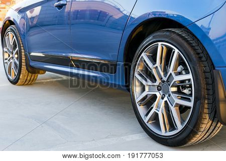 Tire and alloy wheel of a modern blue car on the ground car exterior details
