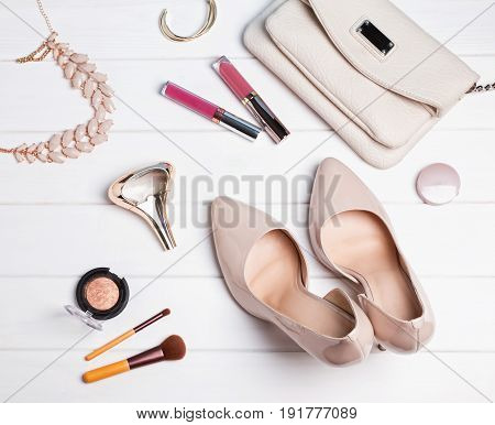 Beige color feminine accessories on the white wooden table, top view