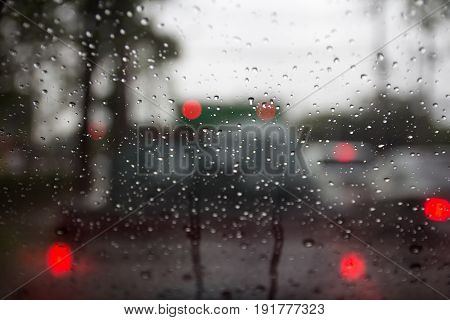 blury car stopped on traffic lights waiting for go on in rainy day with bokeh on windshield