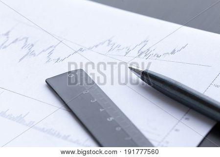 Pen showing diagram on financial report. Studio shot