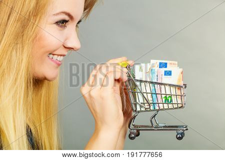 Economy buying things customer concept. Happy smiling woman holding shopping cart with euro money inside