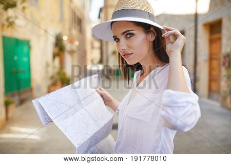 Young beautiful female traveler standing on the street and looking at the map