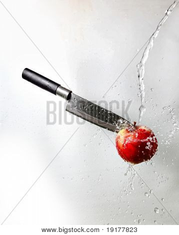 Knife embedded in the apple in the flow of water