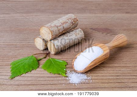 sugar substitute xylitol a scoop with birch sugar liefs and wood on wooden background