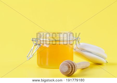 Jar of Honey with Honey Dipper on yellow
