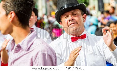 Banos De Agua Santa Ecuador - 29 November 2014: Political Hispanic Man From Ecuador With White Shirt And Red Tie Dancing On The Street Of Banos De Agua Santa South America On November 29 2014