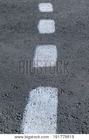 On the gray asphalt paint marking. Rough intermittent white line. Dashed markings divide the road in half.