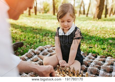 Anonymous senior man sitting on plaid with granddaughter playing chess in park.