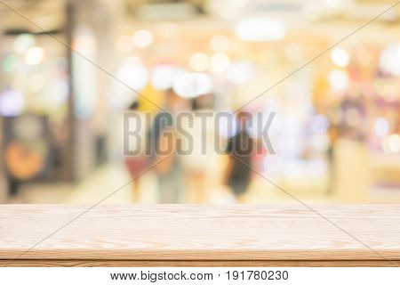 wood coordination table top on shopping mall blurred background,Space available for the product