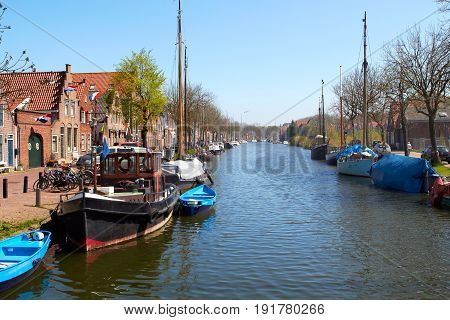 Traditional Dutch Botter Fishing Boats in the small Harbor of the Historic Fishing Village of Spakenburg-Bunschoten in the Netherlands. The village was at one time a harbor on the inland sea. Sprinf sunny day