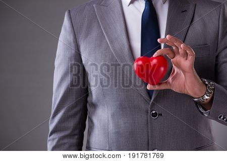 Businessman holding red heart in love concept