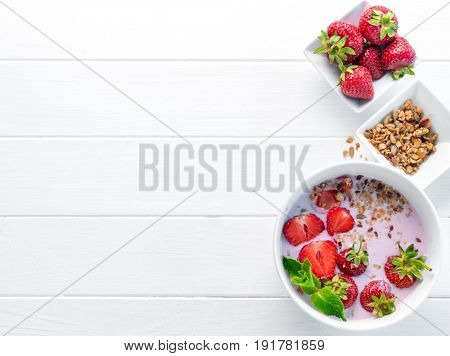 Nutritious breakfast with granola and strawberries, peanuts in a bowl, copyspace left on side, topview
