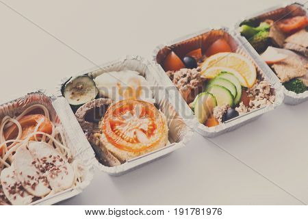 Healthy eating. Organic restaurant food delivery. Daily fitness menu. Dietary steamed meat with garnish and vegetable salads in boxes on white background, vintage filter