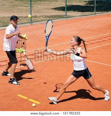 Young woman with instructor on cardio tennis training