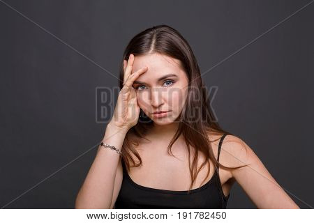 Portrait of young woman having headache. Attractive girl with migraine touching her head, dark background
