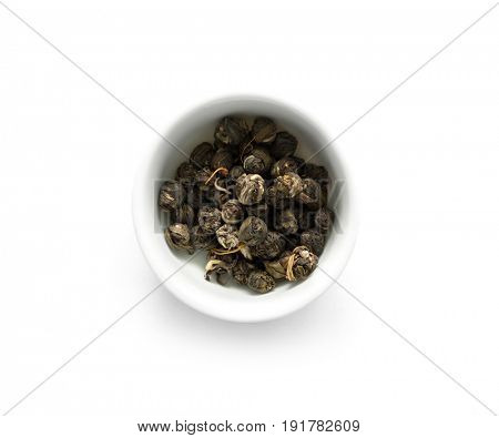 Green jasmine tea in white simple bowl, little pieces of tea, compressed together, topview
