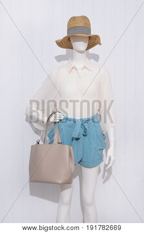 female blue clothing with hat and bag on mannequin female blue clothing with hat and bag on mannequin