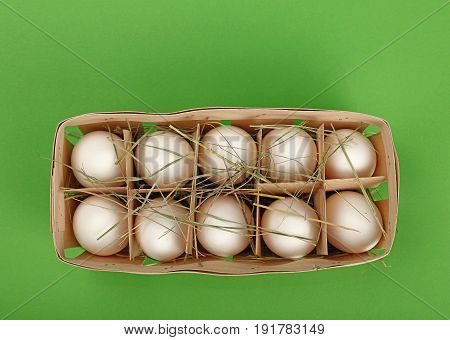 White Chicken Eggs In Wooden Container Over Green