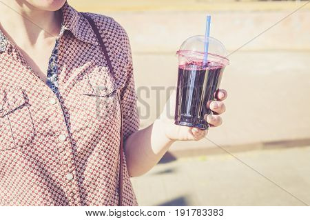 Woman holding berry drink in plastic cup with straw. Summer refreshing takeaway beverages concept. Vintage tone