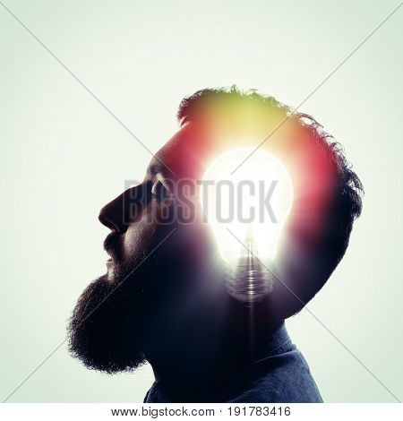 The concept of a new idea. Silhouette of a man's face with a glowing light bulb inside the head.