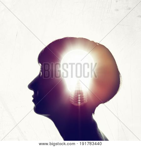 The concept of a new idea. Silhouette of a woman's face with a glowing light bulb inside the head.