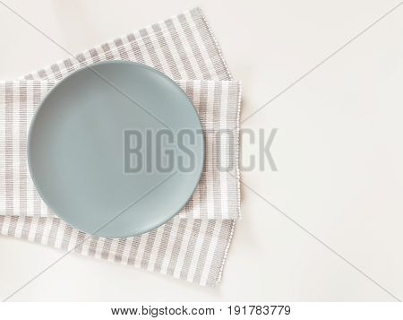 Empty Plate With A Napkin On White Table