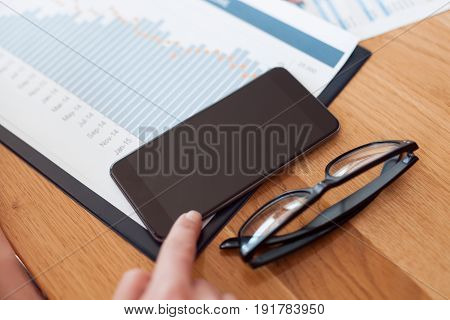 Crop female hand touching smartphone on table with documents and glasses.