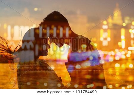 Double exposure of couple silhouette and night cityscape