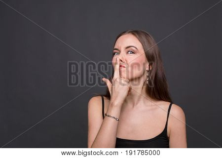 Young woman joking and touching her nose. Funny girl merry and grimacing at camera