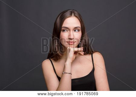 Portrait of thoughtful woman with mysterious look. Pensive girl touch her chin and dreaming, dark background