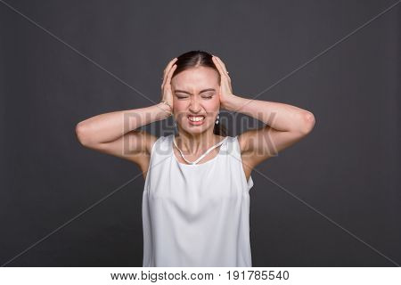 Portrait of angry woman holding her head. Panic, emotional stress, brain explosion concept