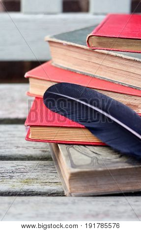 a pile of red and green vintage books with a blck feather pen on a weathered wooden bench