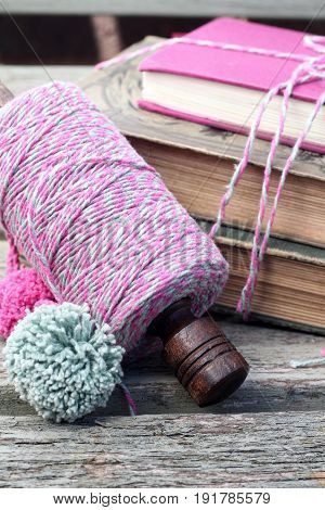 Pink and green twine on a wooden spool , next to a tied up pile of vintage books on a weathered wooden bench