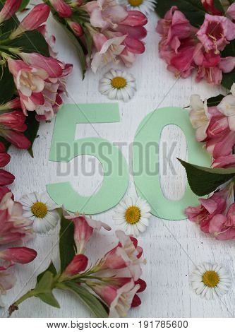 Pale green number fifty surrounded by spring flowers , birthday and anniversary image