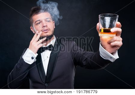 Elegant Young Man Toasting With Glass Of Alcohol