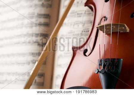 Close-up photo of vintage violin with bow and musical notes. Cello or fiddle and fiddlestick on ancient music sheet rusted old yellow paper sheet of music.