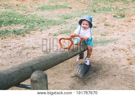 Little boy child playing on a playground. Cute smiling fashionable kid on swing. Happy family on playground at summer day in a park. Leisure childhood and people concept.