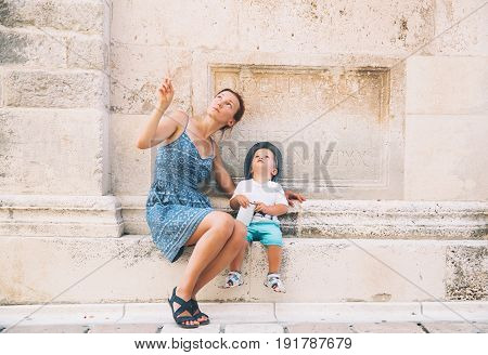 Mother and son in Zadar Croatia. Summer holidays on the seacoast of Europe. Tourists walking on the old historical streets of Zadar. Lifestyles Family Vacation and Travel concept.