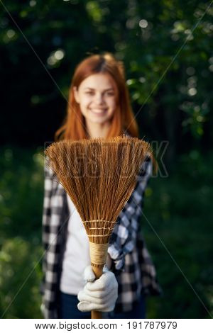 Woman with a broom, a woman doing cleaning in the garden, cleaning.